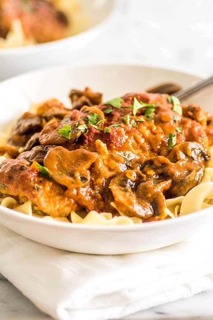 This Easy Chicken Cacciatore is boneless, skinless chicken thighs and mushrooms simmered in a rich tomato sauce and served over a bed of egg noodles for a fabulous weeknight meal. | Easy Dinners | Easy Pasta | Chicken Pasta |