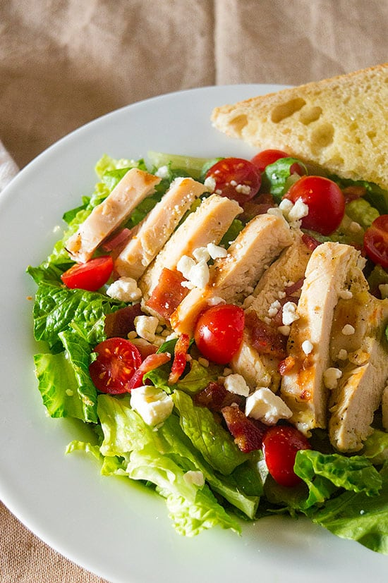 My favorite hearty chicken salad, loaded with garlic chicken, tomatoes, bacon, and feta. So good, you won't mind eating your greens! Recipe includes nutritional information and make-ahead instructions.