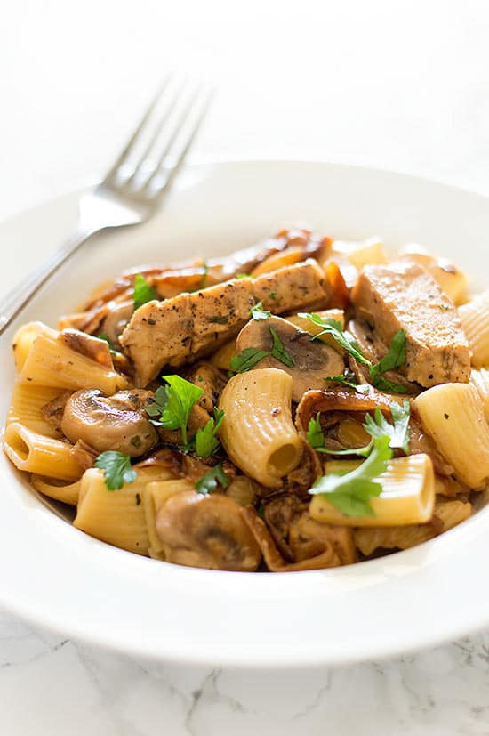 Lightened Up Copycat Carmela's Chicken - Chicken, mushrooms, and delicious caramelized onions cooked up in a wine and cream sauce and served over rigatoni. A lightened up version of the Macaroni Grill favorite. Recipe includes nutritional information, make-ahead and low-yield instructions. From BakingMischief.com