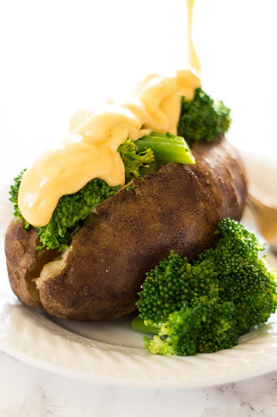 Slow Cooker Baked Potatoes With Broccoli and Cheese Sauce - Slow cooker baked potatoes piled high with broccoli and a glorious cheddar cheese sauce. Perfect for Meatless Mondays! Recipe includes nutritional information and small-yield instructions. From BakingMischief.com