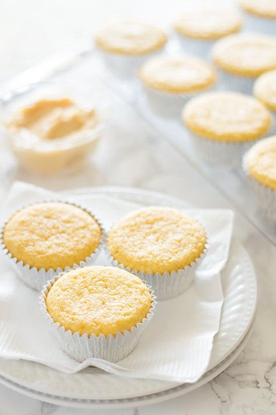 Three cornbread muffins on a plate.