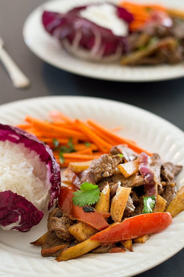 Lomo Saltado is tender stir-fried beef sirloin, red onions, and tomatoes served with baked french fries and white rice. Carb lovers, you have to try this one! Recipe includes nutritional information. From Baking Mischief.com