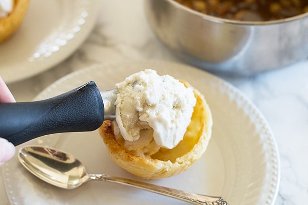Apple pie in sundae form! Tart Granny Smith apples cooked with brown sugar and cinnamon and dowsed in caramel sauce. Served over vanilla ice cream in a flaky homemade (easy!) buttermilk pie crust shell. Recipe includes nutritional information. From BakingMischief.com