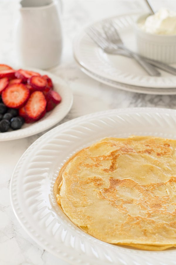 Classic crepes for two stuffed full of whipped cream, strawberries, and blueberries and topped with strawberry syrup make a perfect patriotic breakfast. Recipe includes nutritional information. From BakingMischief.com