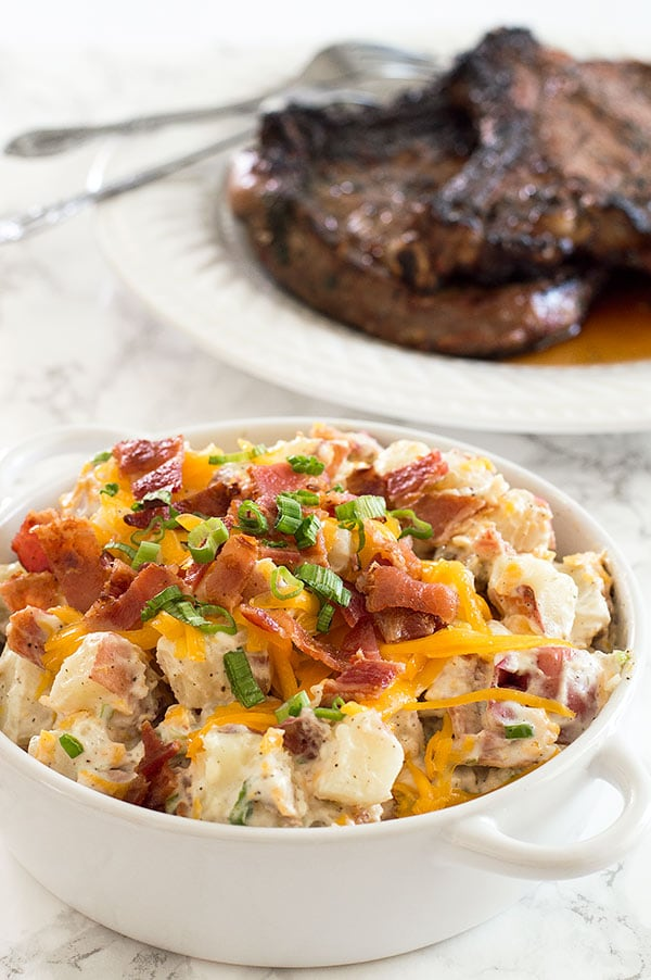 Creamy, cheesy loaded baked potato salad lightened up a bit with Greek yogurt (you'll never know it's there!). Recipe includes nutritional information. From BakingMischief.com