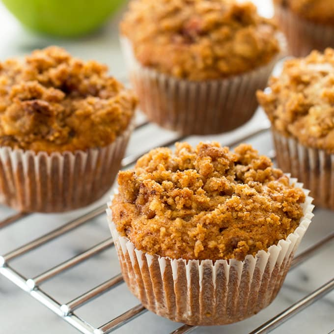 Tender apple crumb muffins with caramelized cinnamon apples and a crunchy crumbly brown sugar crumb topping. Recipe includes nutritional information. From BakingMischief.com