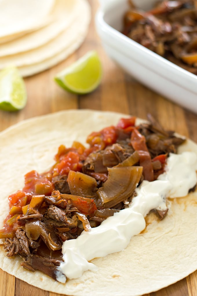 Easy slow cooker beef fajitas are a fantastic, cheap, and simple dinner for busy weeknights! Recipe includes nutritional information. From BakingMischief.com