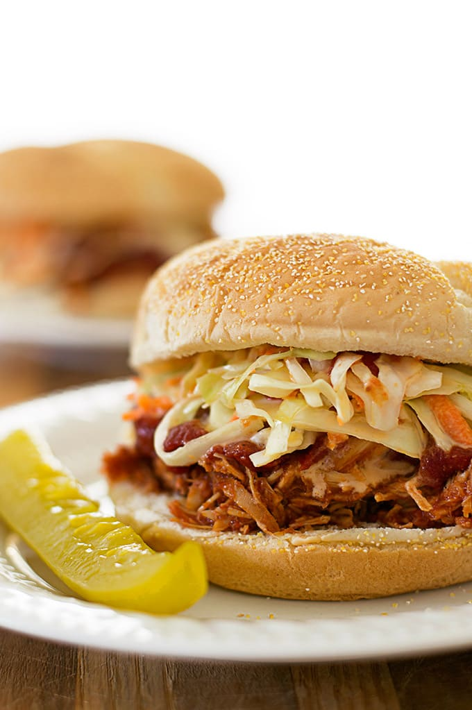 Slow cooker BBQ chicken sandwiches for two with a sweet and tangy homemade tomato BBQ sauce and crunchy coleslaw topping. So easy. So good. From BakingMischief.com
