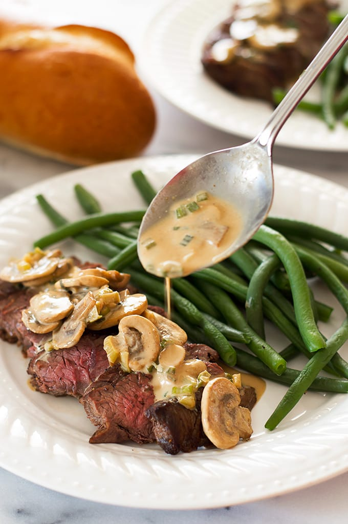 Mustard sauce being drizzled over top sirloin.