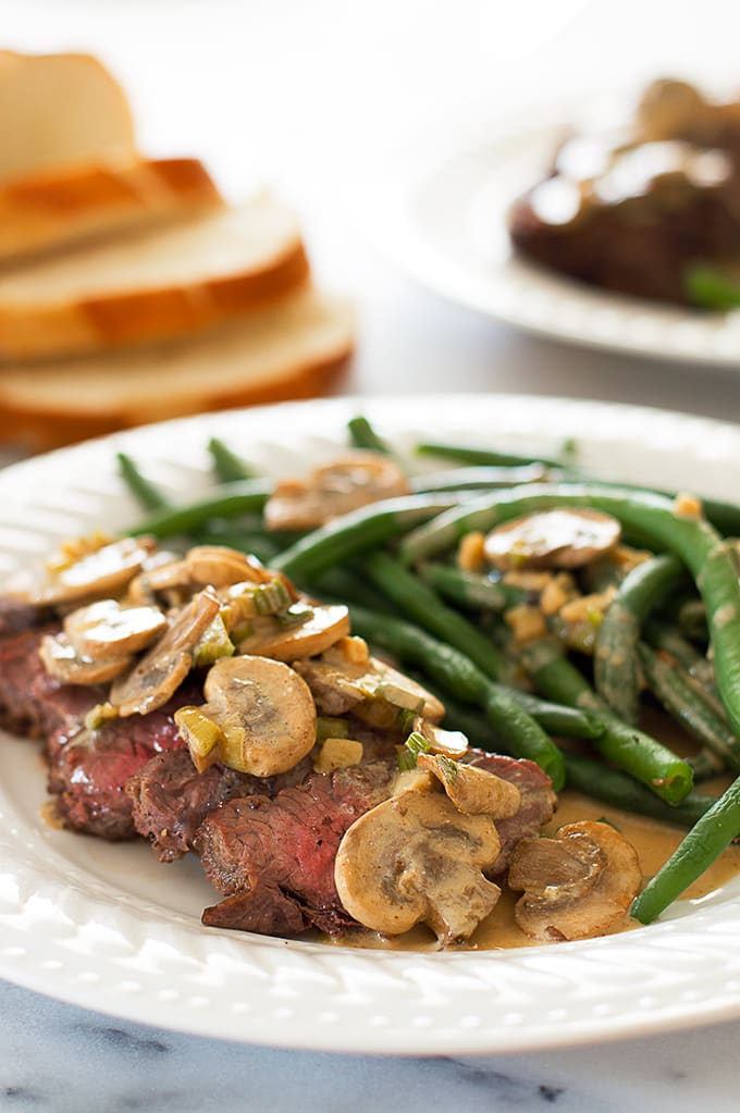 Top sirloin covered with mustard sauce and mushrooms on a plate with green beans.
