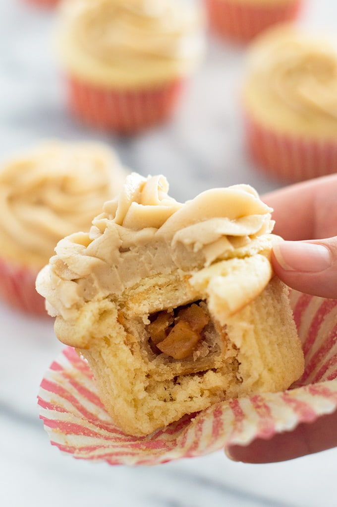 Apple Pie Cupcakes: soft and fluffy vanilla cake wrapped around a miniature apple pie with homemade caramel frosting on top. You're going to love these! From BakingMischief.com