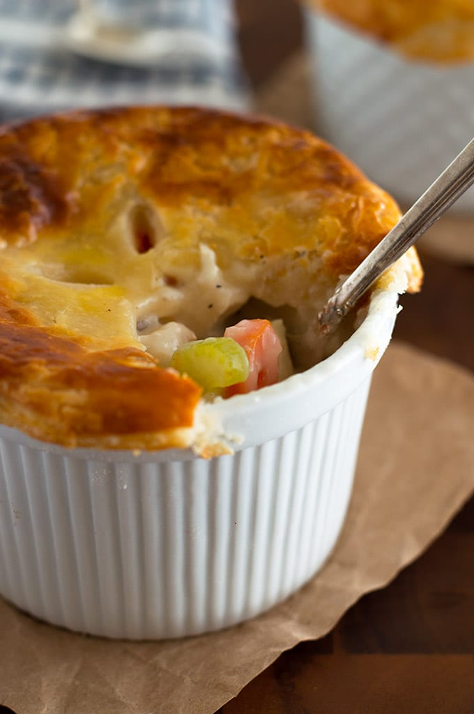 Individual Chicken Pot Pies are a perfect easy dinner for two, stuffed with chicken, carrots, and celery, and topped with a delicious flaky buttermilk crust. From BakingMischief.com