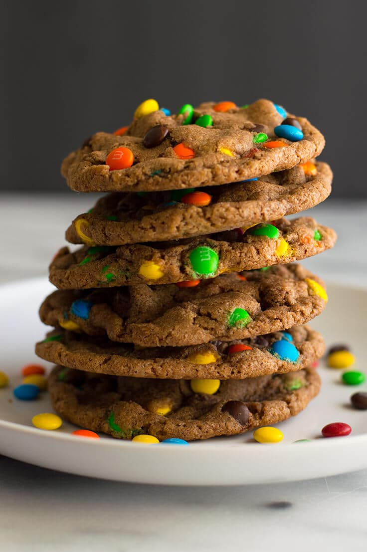 Mini M&M Cookies stacked on a white plate.