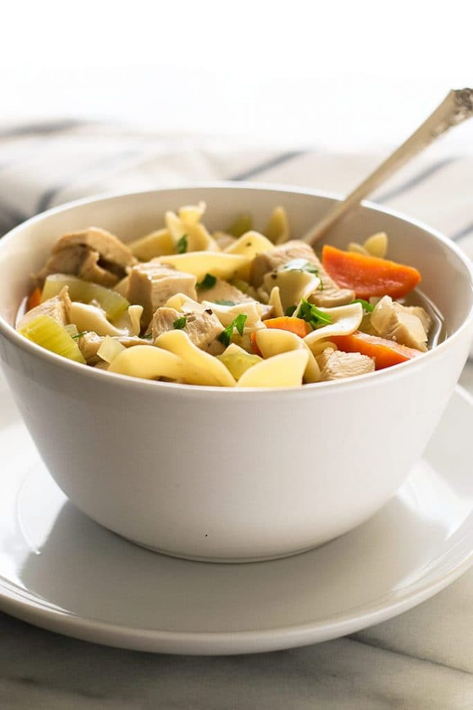 Photo of chicken noodle soup for one in a white bowl with a spoon.