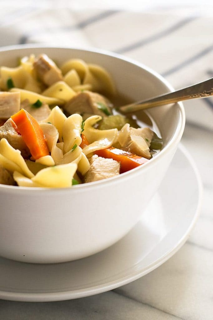 Close up image of chicken noodle soup for one in a white bowl.
