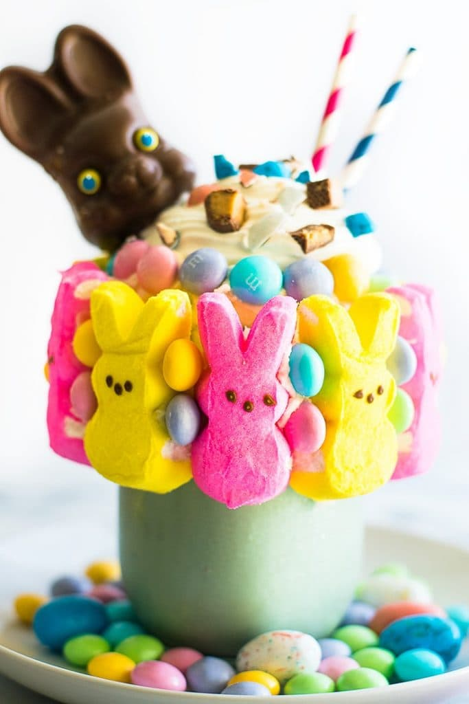 Picture of an Easter Candy Freakshake in a mason jar with candy Peeps stuck to the outside.