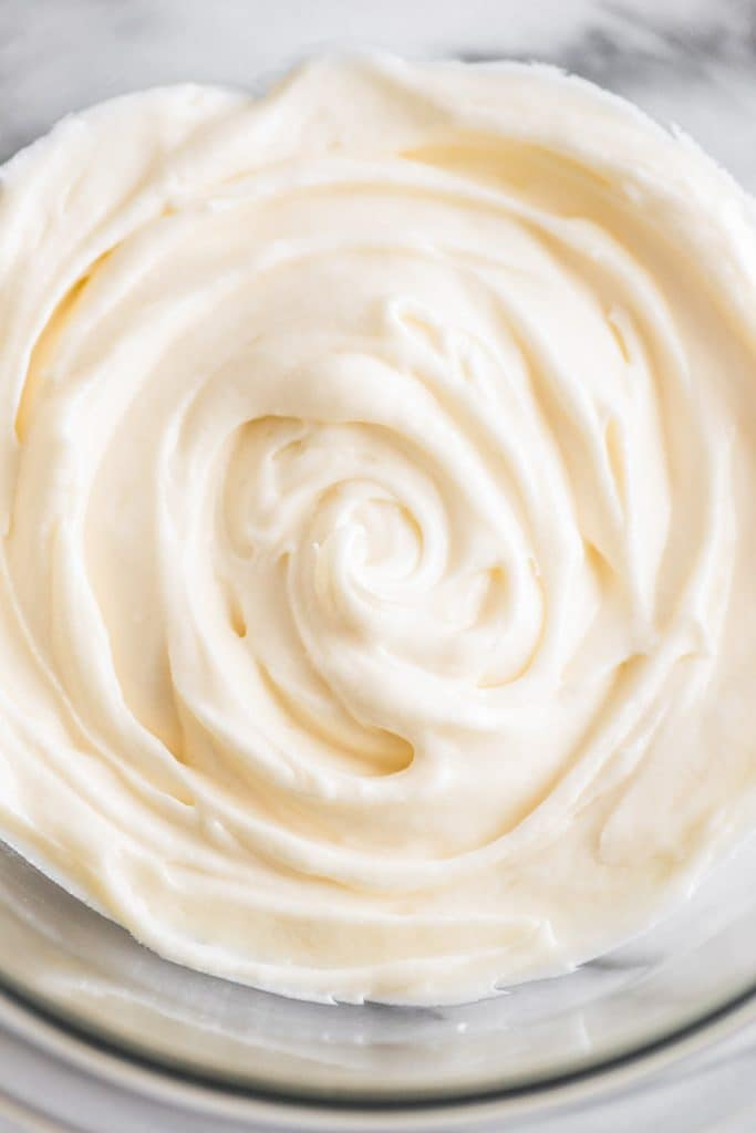 This Small-batch Cream Cheese Frosting recipe is silky smooth, tangy, and very cream cheesy! | #frosting | #creamcheese | #dessert |