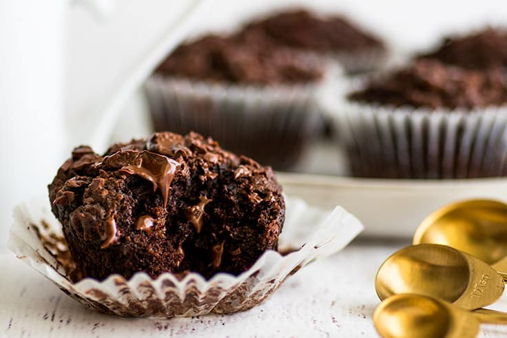 Wide photo of Small-batch Chocolate Banana Muffin with a bite out of it in front of a white mug.