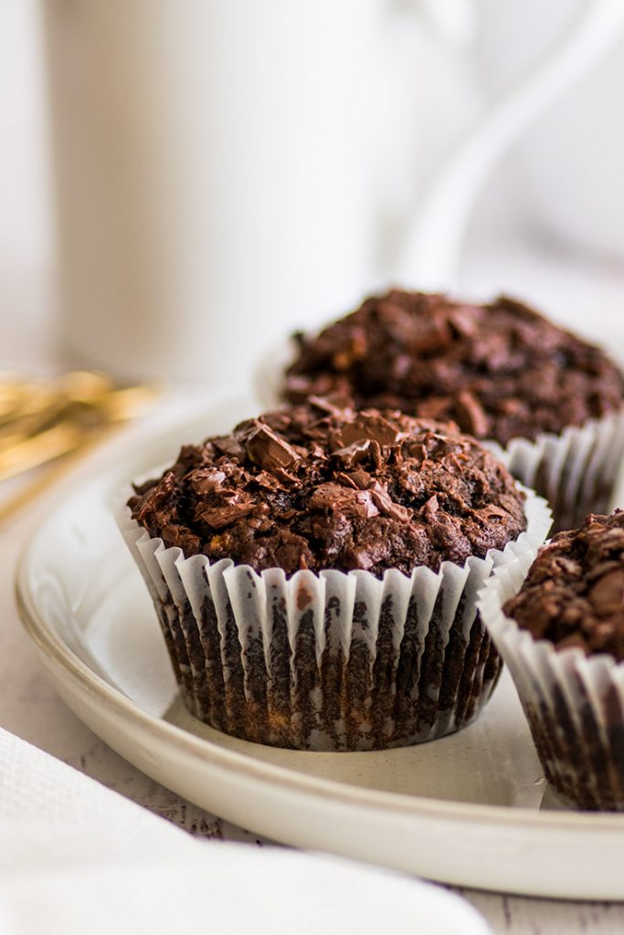 Picture of three Small-batch Chocolate Banana Muffins on a plate. in front of a white mug