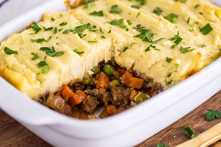 Photo of Easy Shepherd's Pie With Ground Beef in casserole dish with beef, carrot, and pea filling showing.