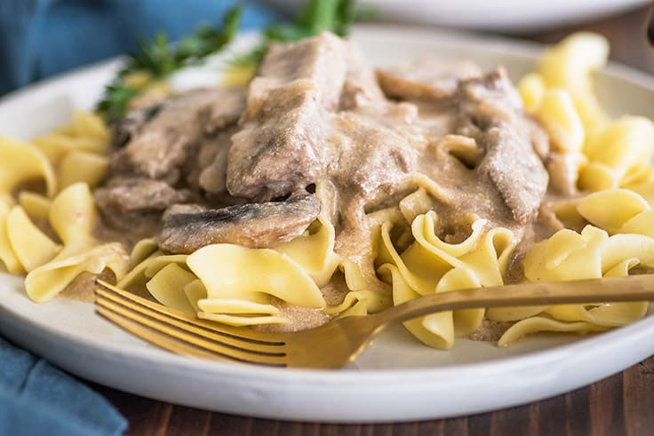 Wide photo of Easy Beef Stroganoff over egg noodles on a plate with a gold fork.