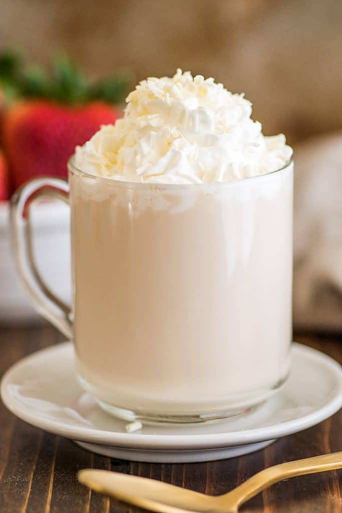 Photo of homemade white chocolate mocha with whipped cream and white chocolate shavings.