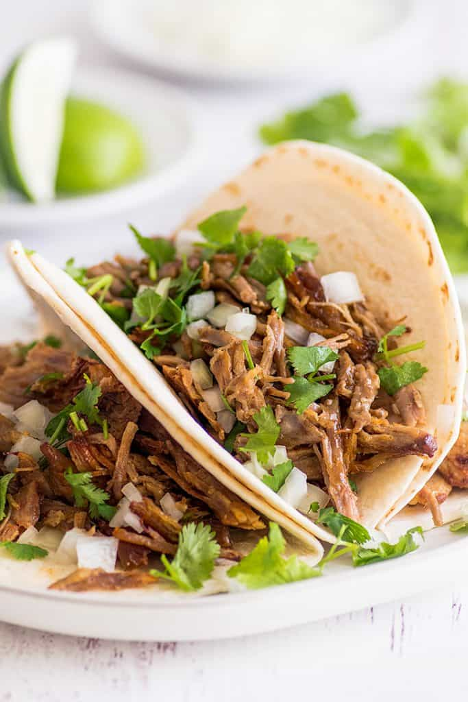 Picture of carnitas made into tacos with cilantro and onion.