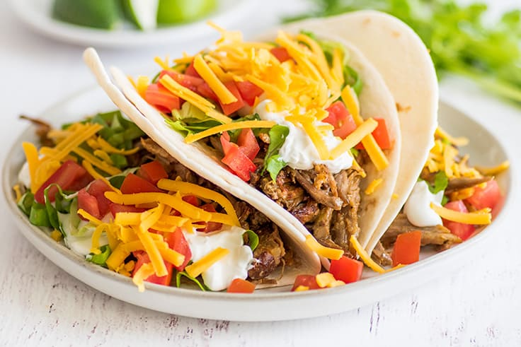 Picture of carnitas tacos with cheddar cheese, sour cream, and tomatoes on a plate.