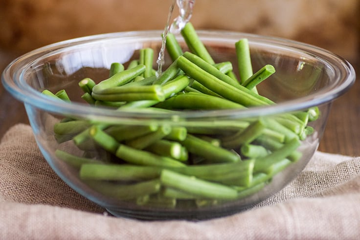Image of How to Steam Green Beans in the Microwave step 1, water being poured over green beans.