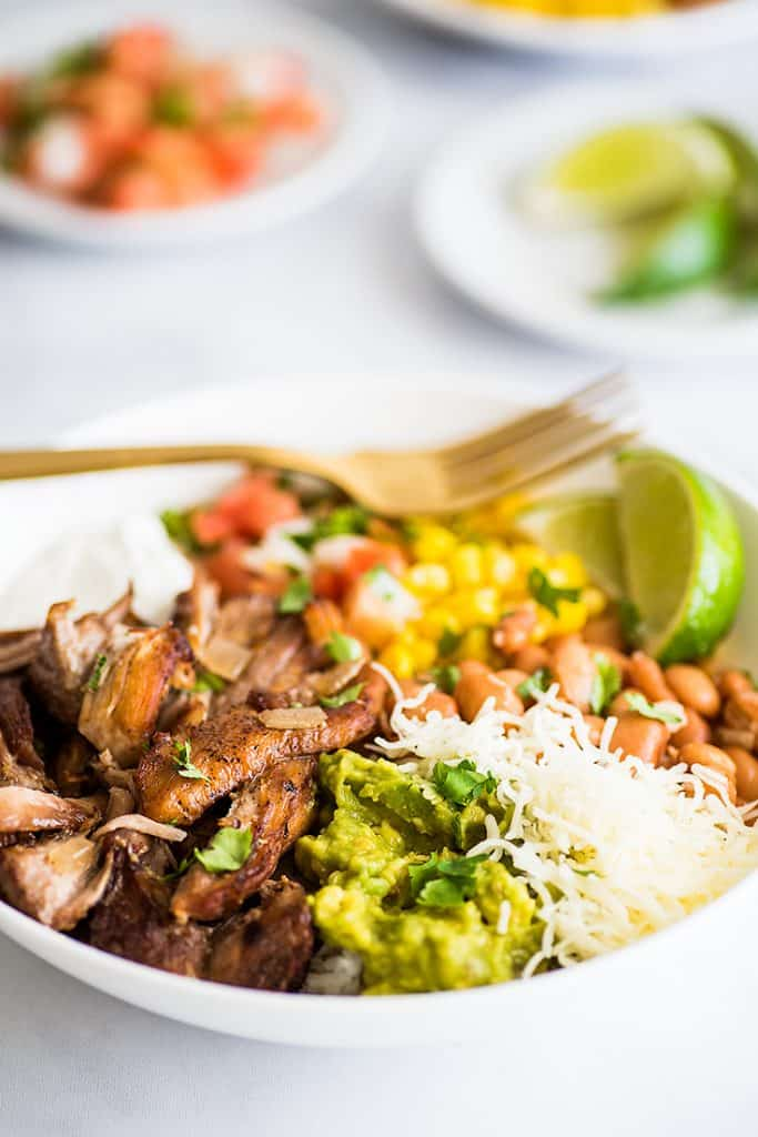 Photo of a Carnitas Burrito Bowl in a white bowl with carnitas, cheese, corn, and guacamole.