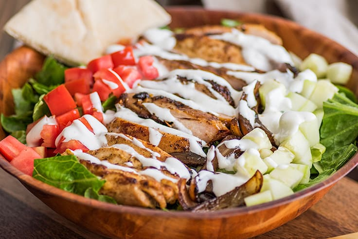 Chicken Shawarma Salad in a bowl drizzled with yogurt dressing.