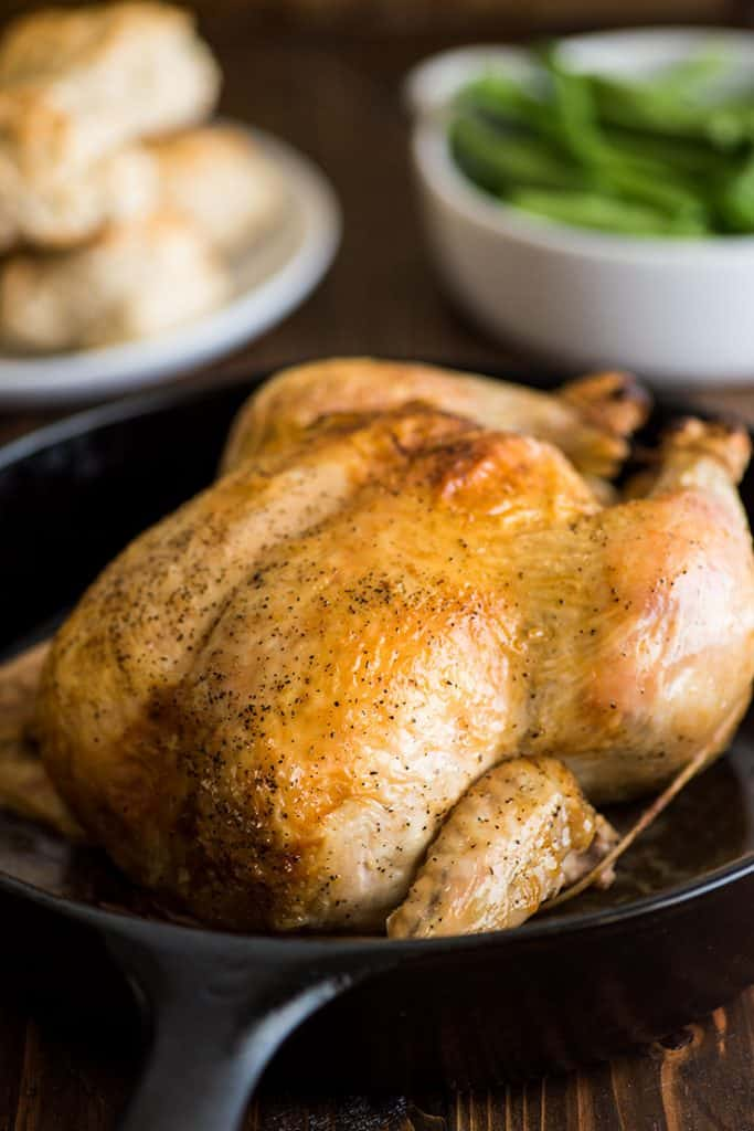 Photo of a whole roasted chicken in a cast iron pan.