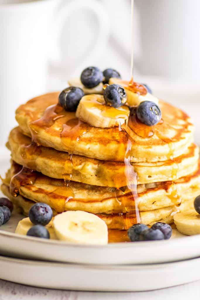 Stack of Easy Banana Pancakes for Two topped with blueberries and banana slices being drizzled with syrup.