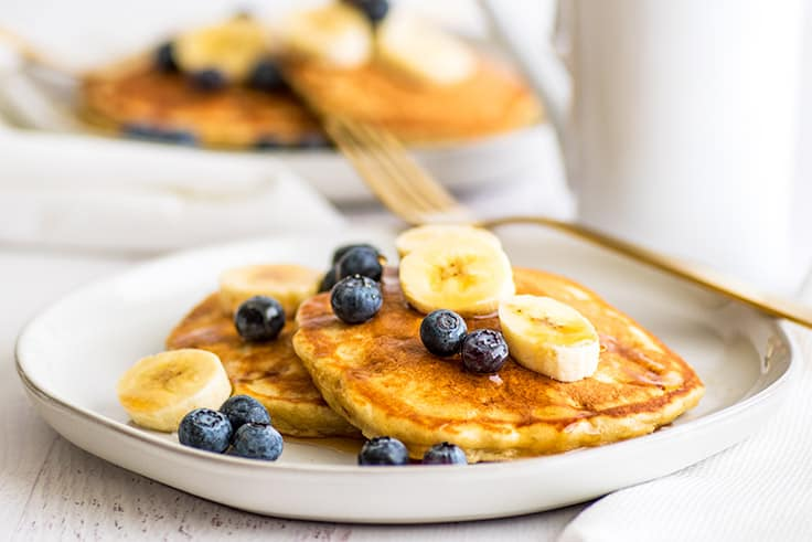 Wide photo of a plate of Easy Banana Pancakes for Two topped with blueberries and banana slices and maple syrup.
