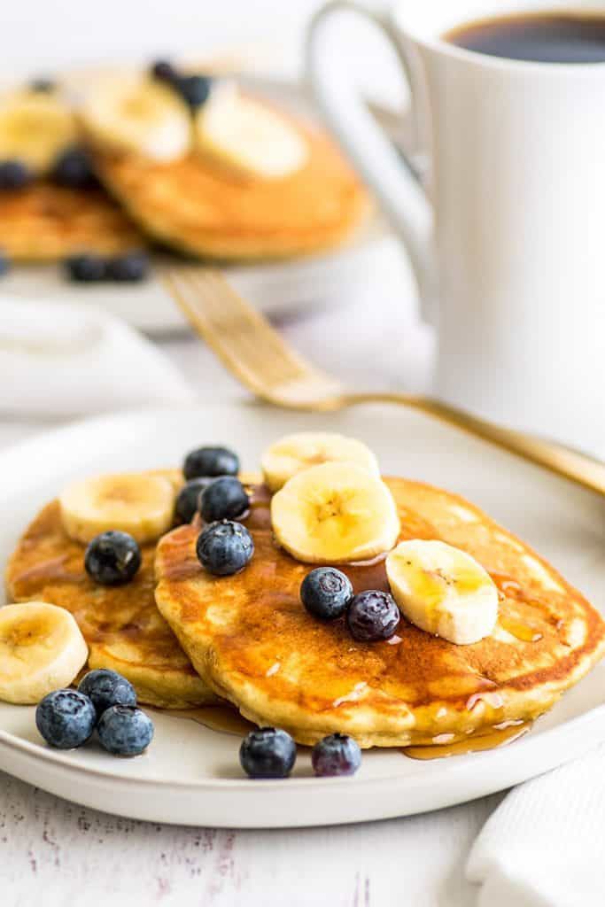 Plate of Easy Banana Pancakes for Two topped with blueberries and banana slices and maple syrup.