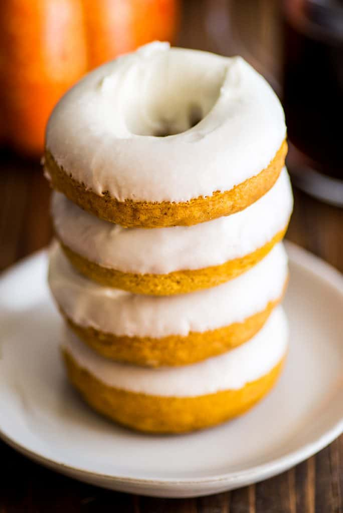 Stack of four baked pumpkin donuts with cream cheese glaze.
