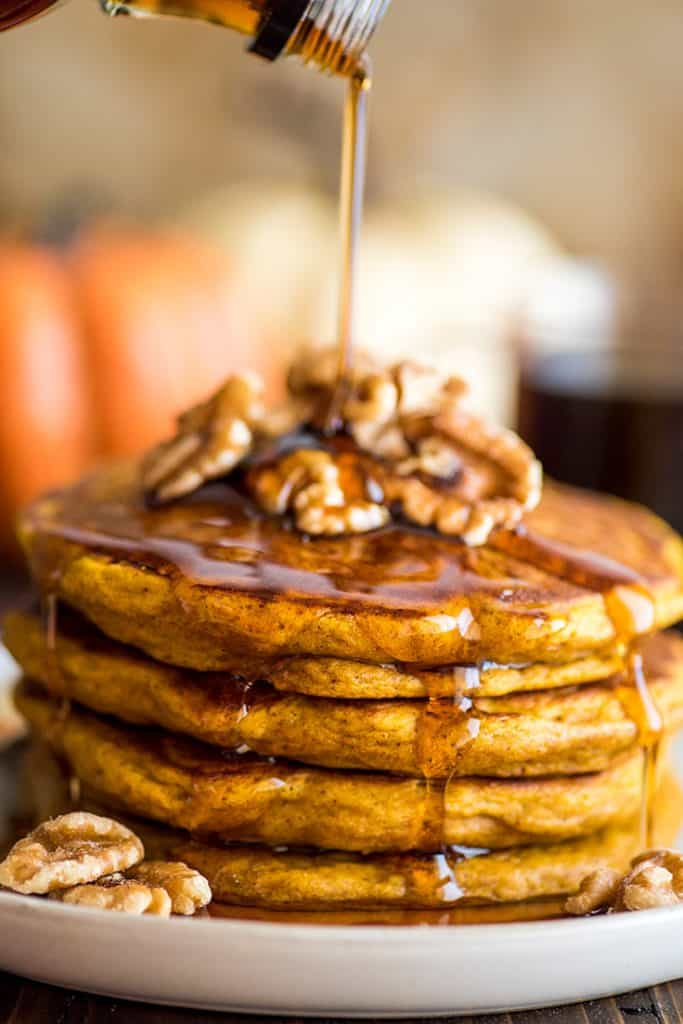 Photograph of syrup being poured over a stack of pumpkin pancakes.