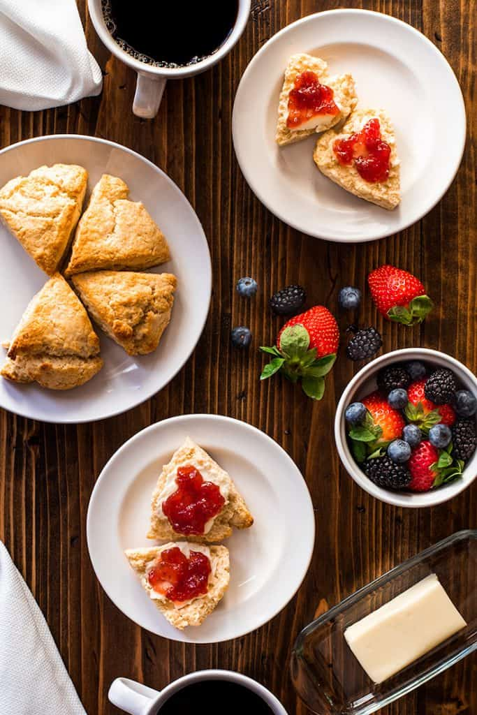Photo over head shot of table with small batch of cream scones and berries.