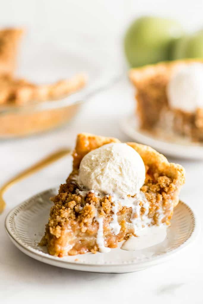 Picture of a slice of Dutch Apple Pie with vanilla ice cream on top.
