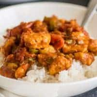 Square photo of Easy Chicken Curry over rice in a white bowl.