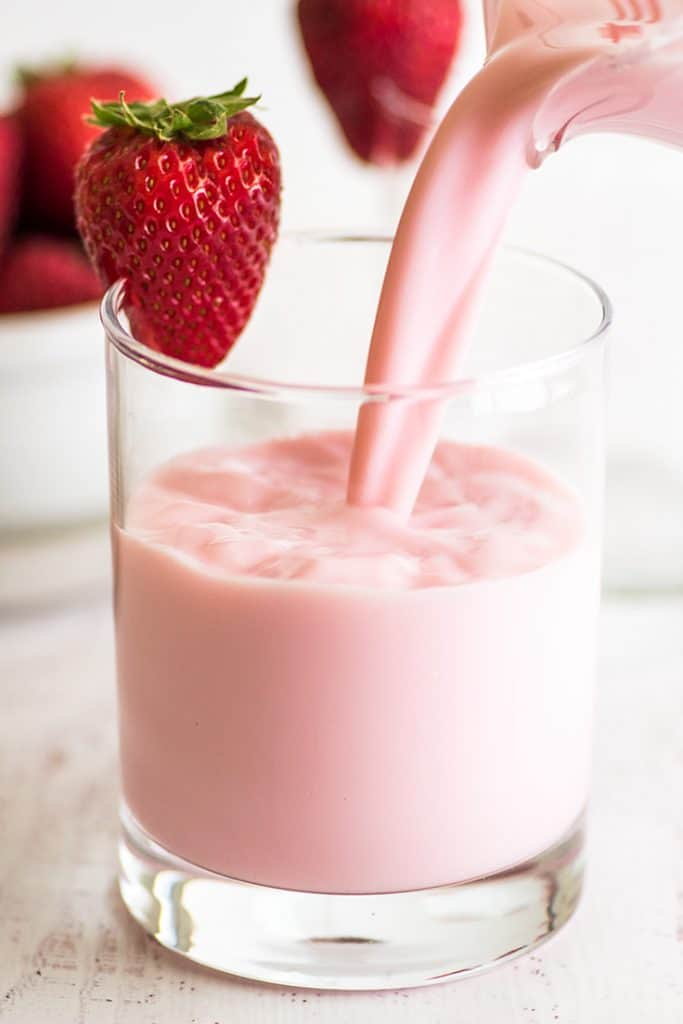 Photo of homemade strawberry milk being poured into a glass.