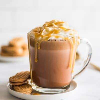 Feature image of Peanut Butter Hot Chocolate on a white plate with Nutter Butter Cookies.