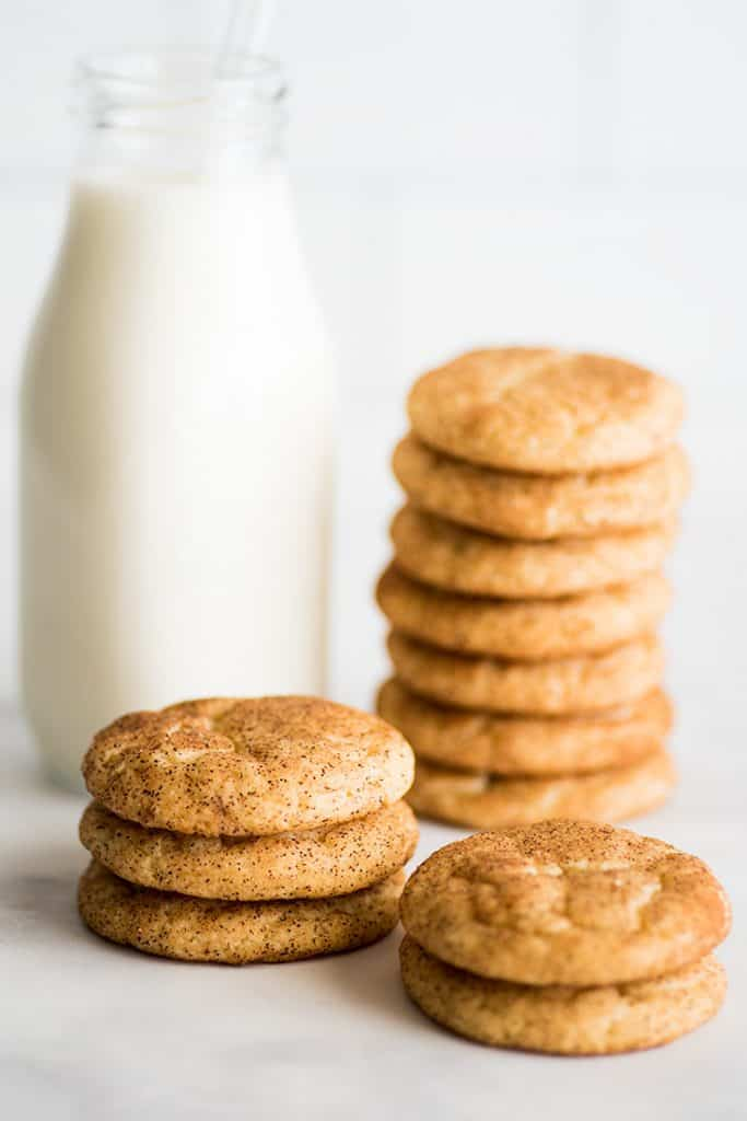 Photo of Snickerdoodle Cookies stacked next to a class of milk.