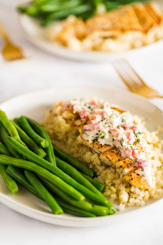 Picture of Keto Chicken in Cream Sauce on a plate over cauliflower rice next to green beans.