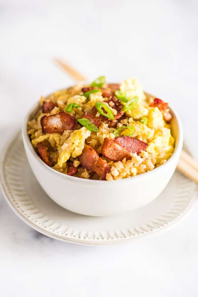 Photo of keto fried rice in a bowl with chopsticks on the plate.