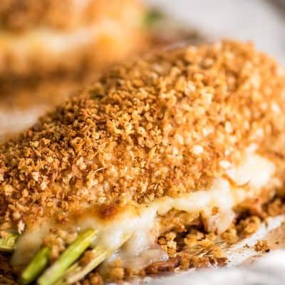 Photo of asparagus stuffed chicken breast filled with mozzarella on a baking sheet.