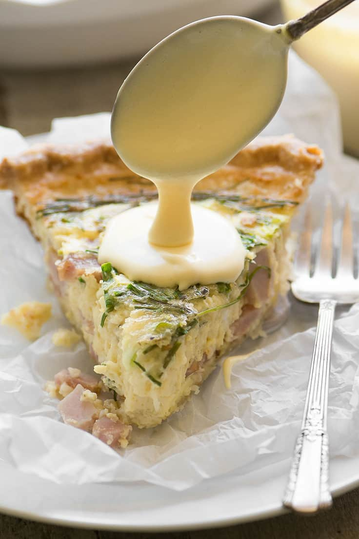 Photo of quiche slice with hollandaise sauce made with egg yolks being spooned over the top.
