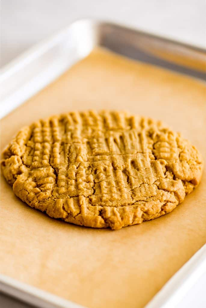 Picture of giant one peanut butter cookie on a quarter sheet baking tray.