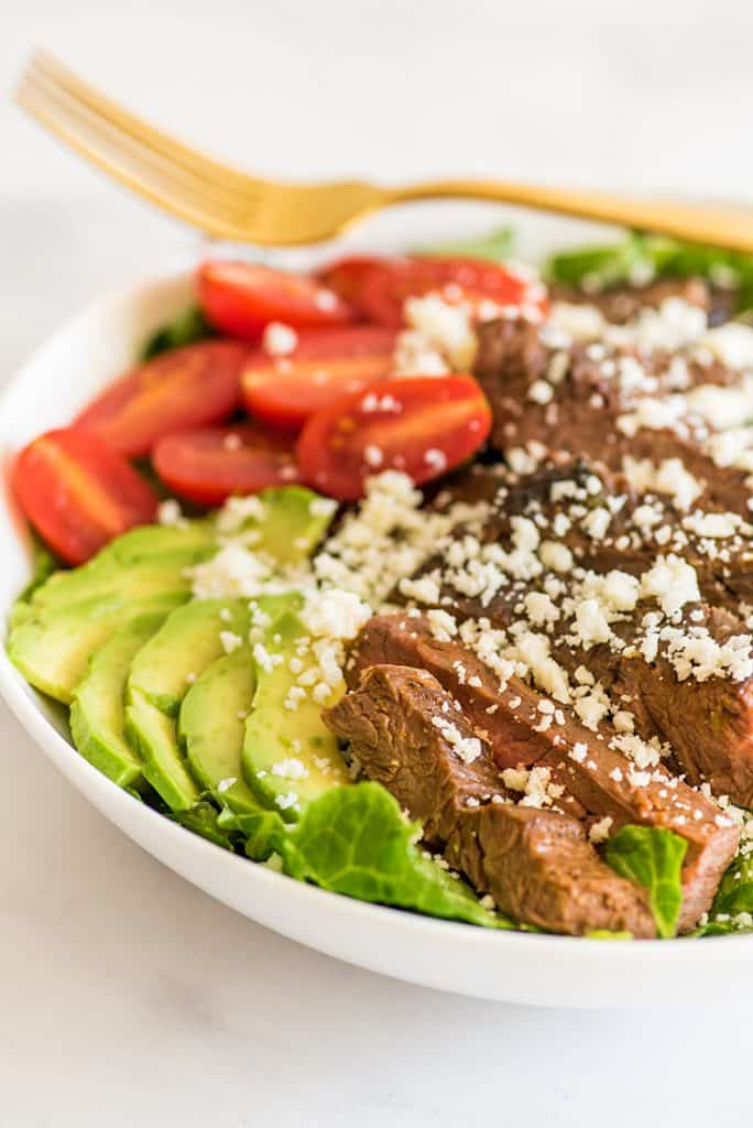 Close up photo of Carne Asada Salad in a white bowl.
