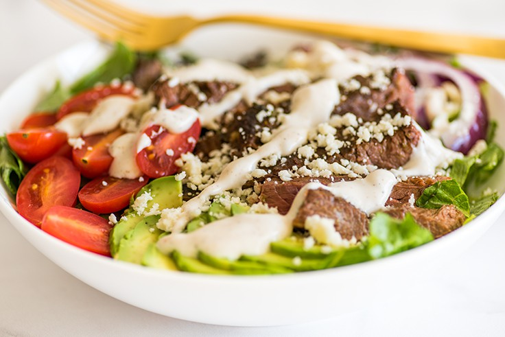 Photo of Carne Asada Salad in a white bowl with chipotle lime yogurt dressing.